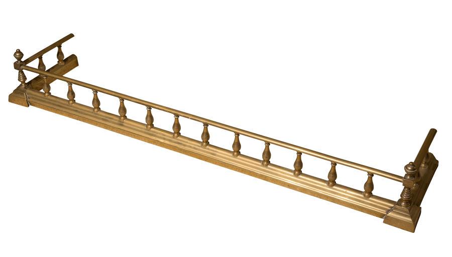 An Edwardian brass fire fender